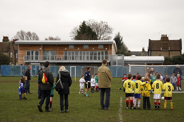 Parents and volunteers look on from the touchline